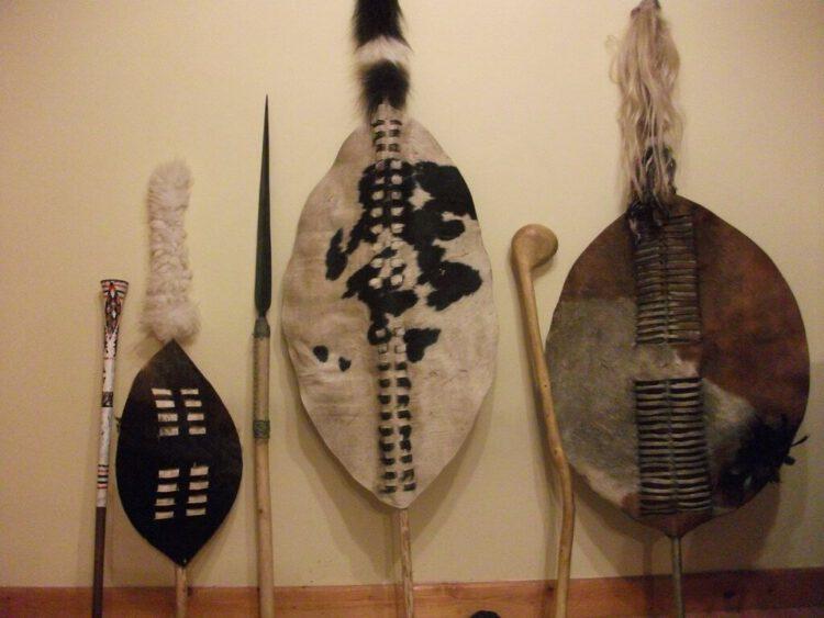 Традиционные военные щиты и копье ассегай (посередине).