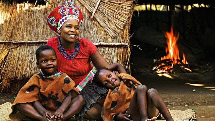 Зулусская женщина в традиционном головном уборе со своими детьми
